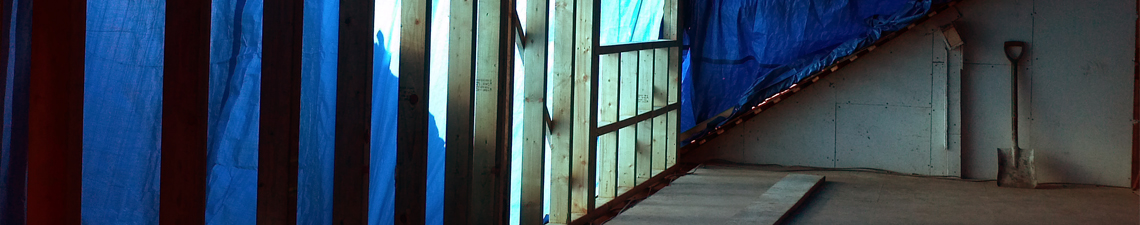 inside empty room surrounded by errected wooden beams covered with a sheet of blue tarpauline
