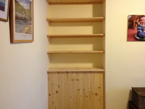 Alcove with fitted pine shelving and cupboard
